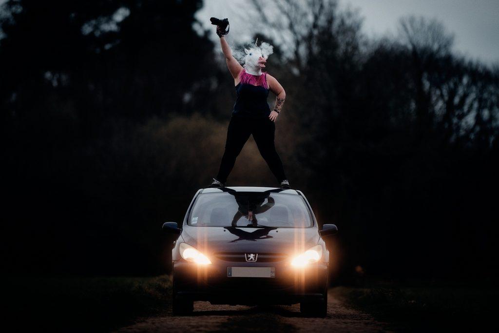 Portrait professionnel d'une photographe de mariage décalée : la photographe se tient sur le toit de sa voiture avec un masque de licorne