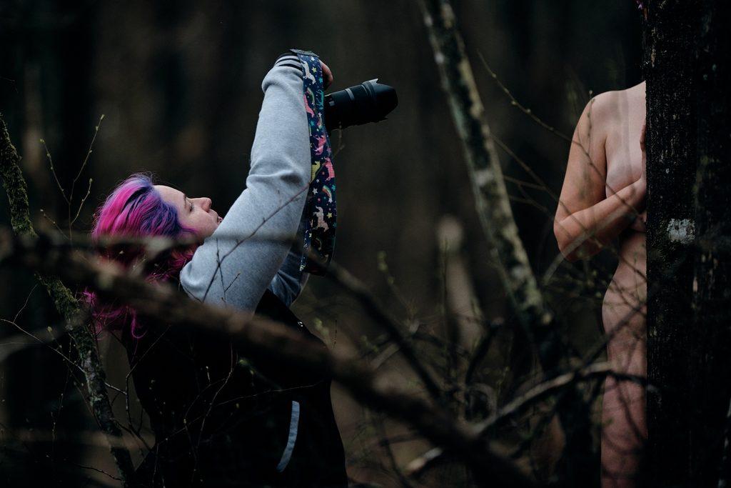 Photographe prenant en photo une modèle que l'on devine entre deux arbres