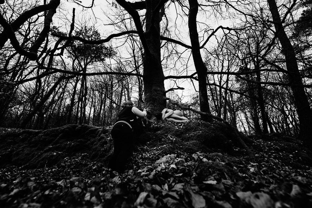 Photographe prenant en photo une femme nue dans la forêt