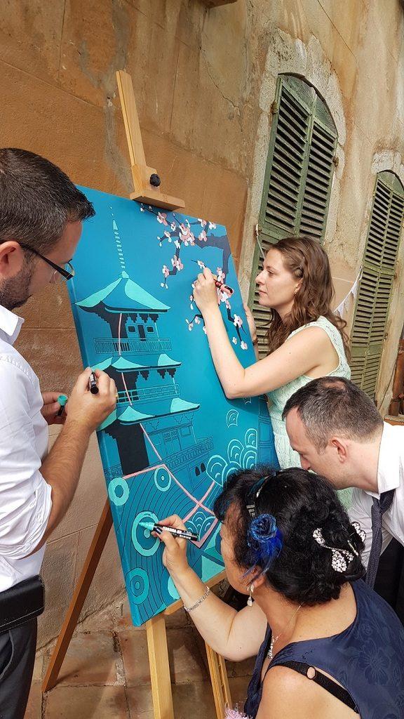 Invités de mariage en train de peindre une toile participative