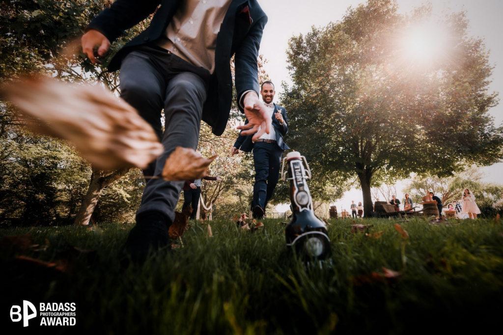 Groupe de garçons d'honneur d'un mariage courant pour attraper une bière posée au sol. Photo récompensée dans le concours badass photographers par un award