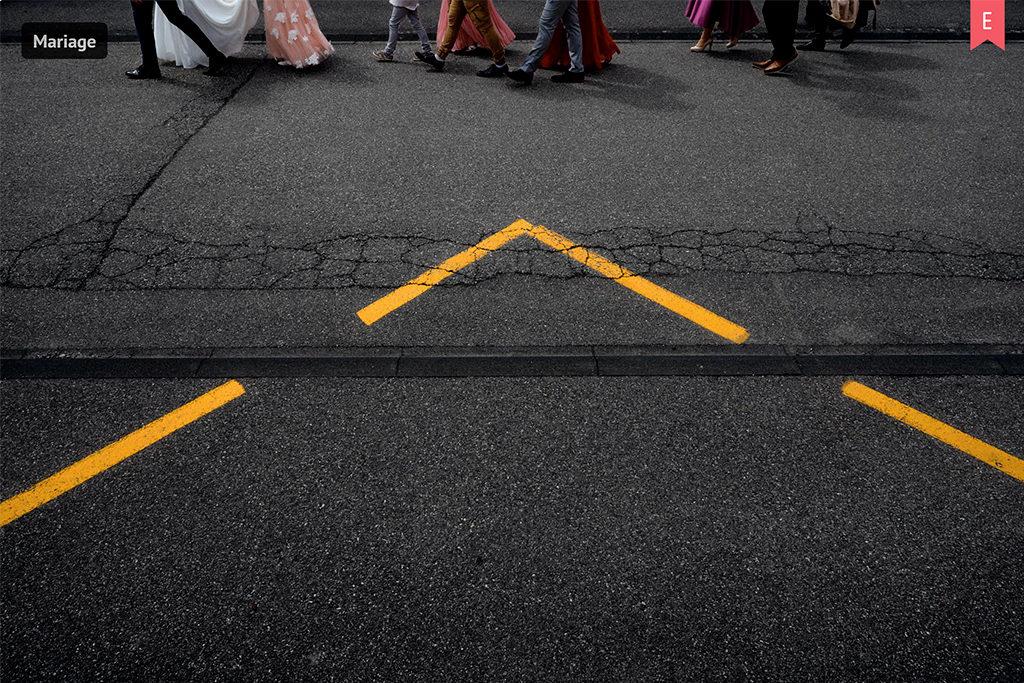 Cortège de mariage se déplaçant vers le lieu de réception. Seuls les pieds sont visibles et un triangle jaune au premier plan se dessine grâce aux lignes d'un arrêt de bus