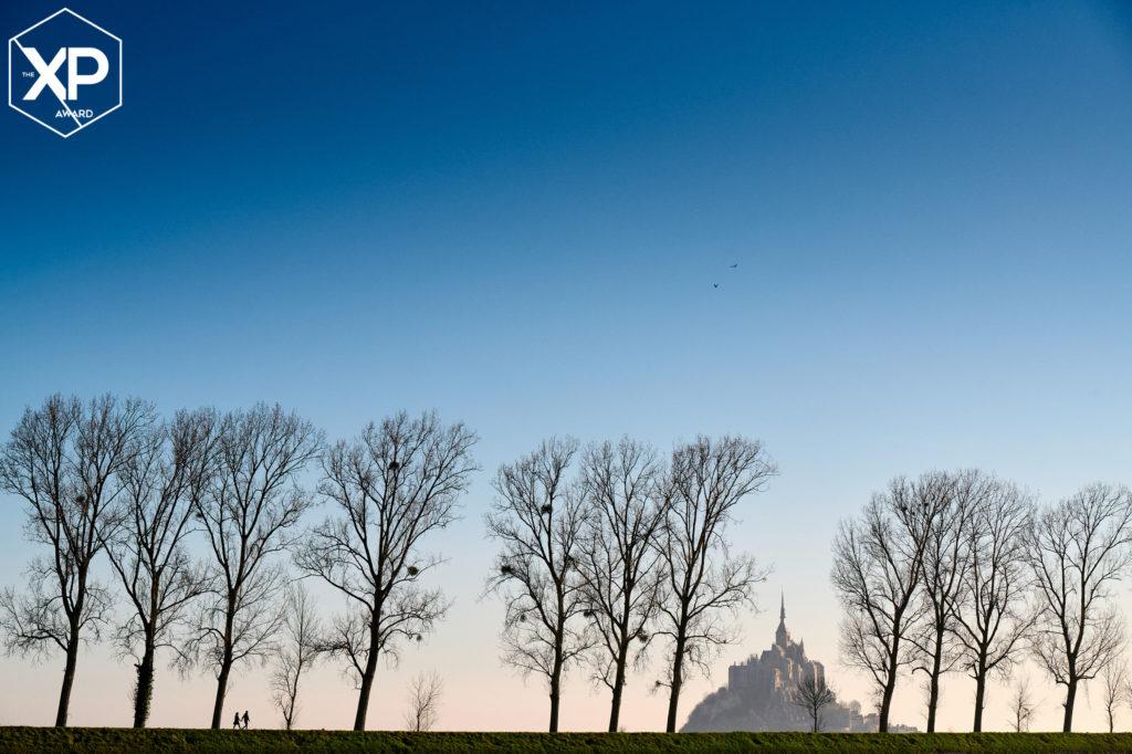 Couple marchant au loin entre les arbres, avec le mont saint michel au loin