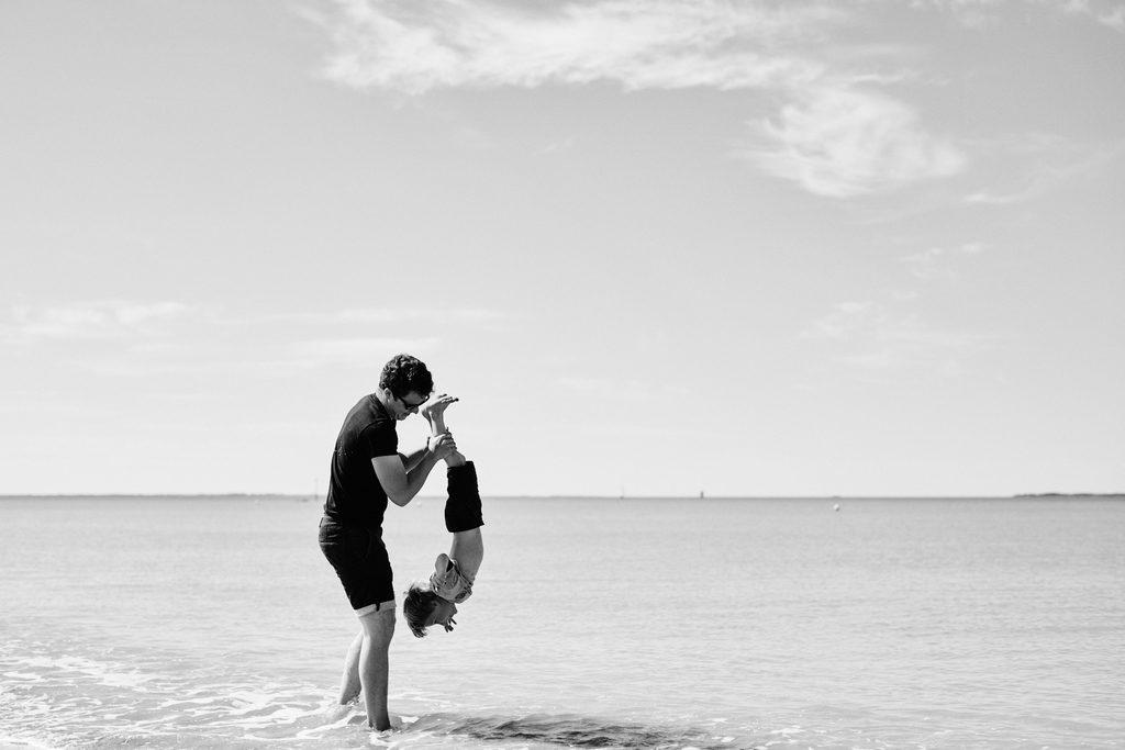Père en train de jouer avec son enfant au-dessus de l'eau