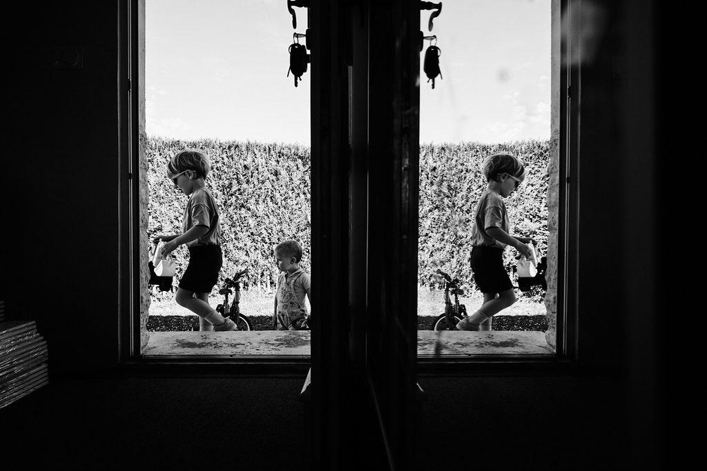 Sur la gauche on voit les deux enfants à travers la porte d'entrée, sur la droite on ne voit que le reflet du plus grand