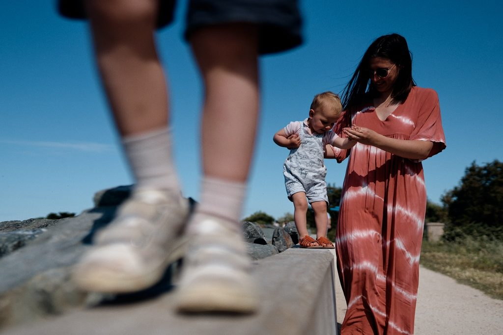Maman en train d'aider sa fille à marcher sur un muret. Au premier plan on voit les pieds de l'ainé sur le muret