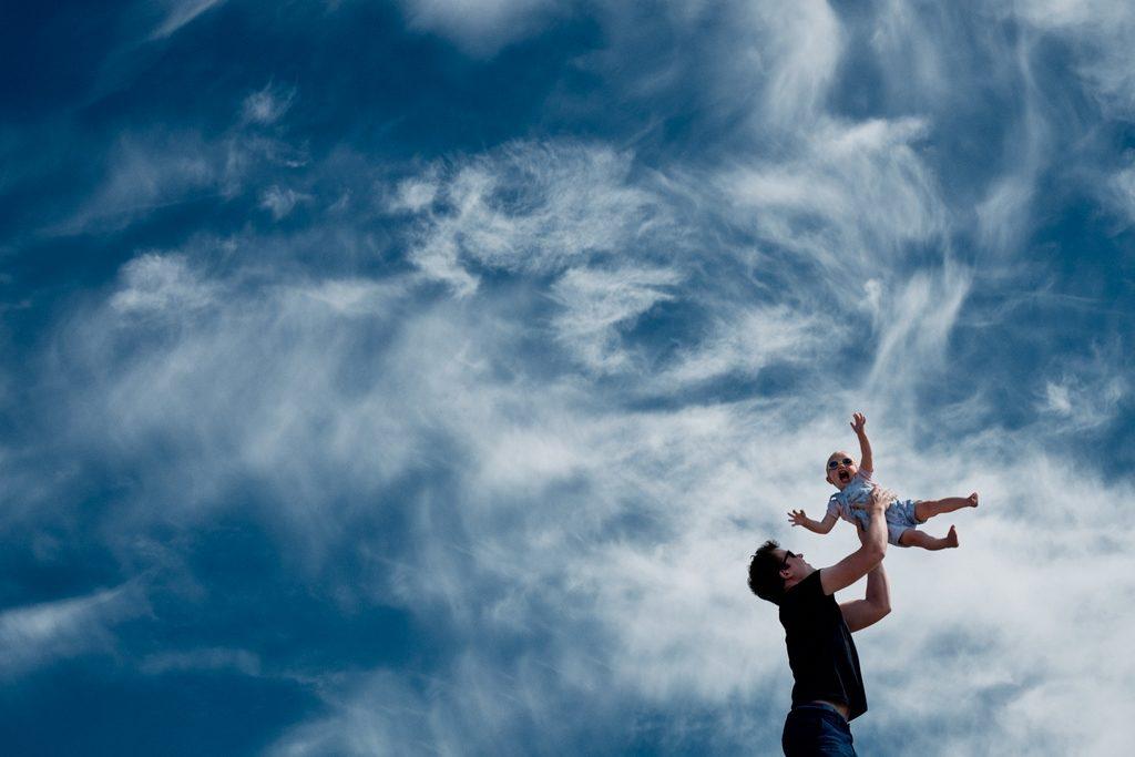 Père en train de jouer avec son enfant en la jetant en l'air