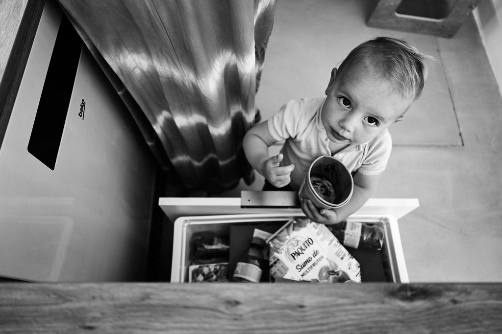 Petite fille en train de faire une bêtise en fouillant dans la poubelle de tri
