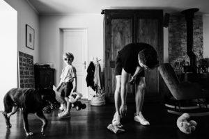 Photo de reportage famille, un enfant marche dans la pièce tandis que le père ramasse les jouets. Le chien passe lui aussi dans le cadre