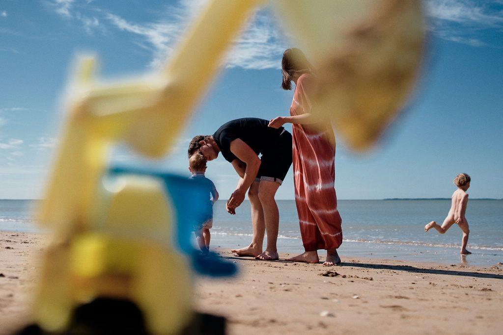 Enfant courant vers la mer pendant que ses parents s'occupent de sa petite soeur. Un jouet au premier plan forme un cadre dans l'image