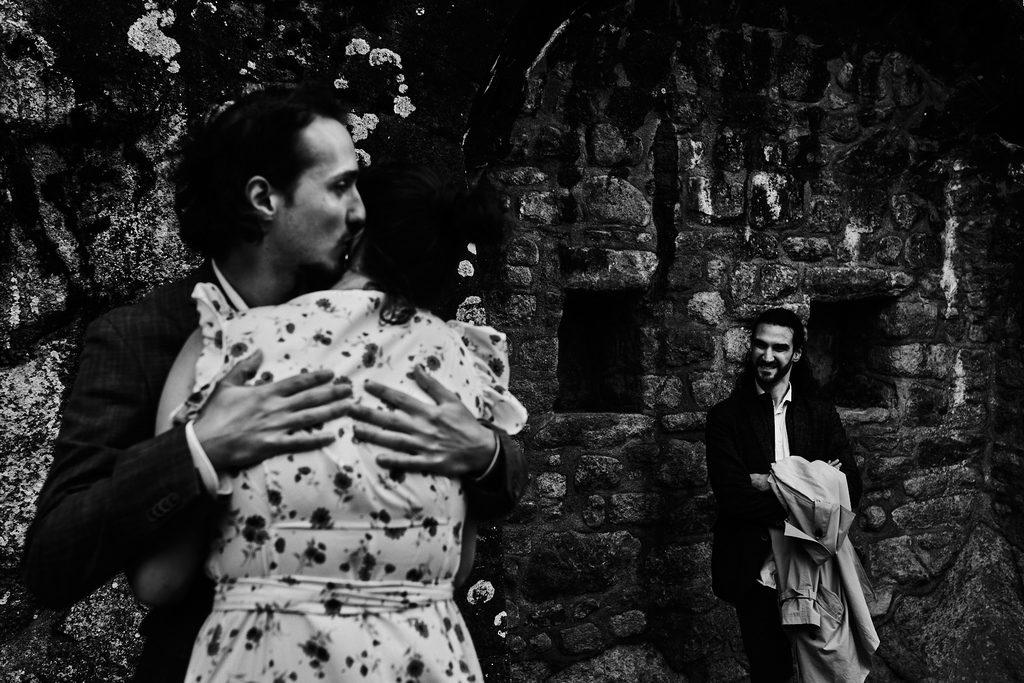 Photo de deux amoureux s'embrassant sous le regard plein de compersion d'un troisième amoureux